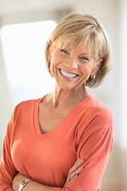 woman wearing coral shirt smiling