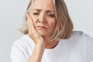 woman experiencing painful dental implant failure