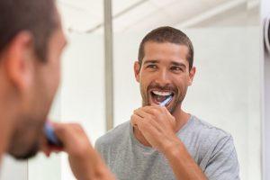 a person brushing their teeth in a bathroom